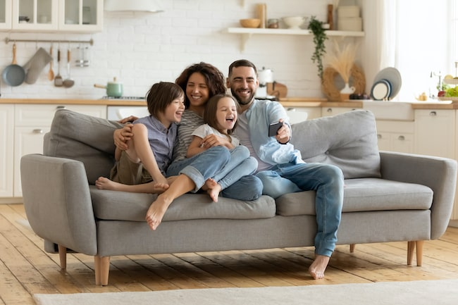 happy family sitting on a couch and laughing watching something on a phone